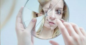Woman looks at her own reflect via a broken mirror
