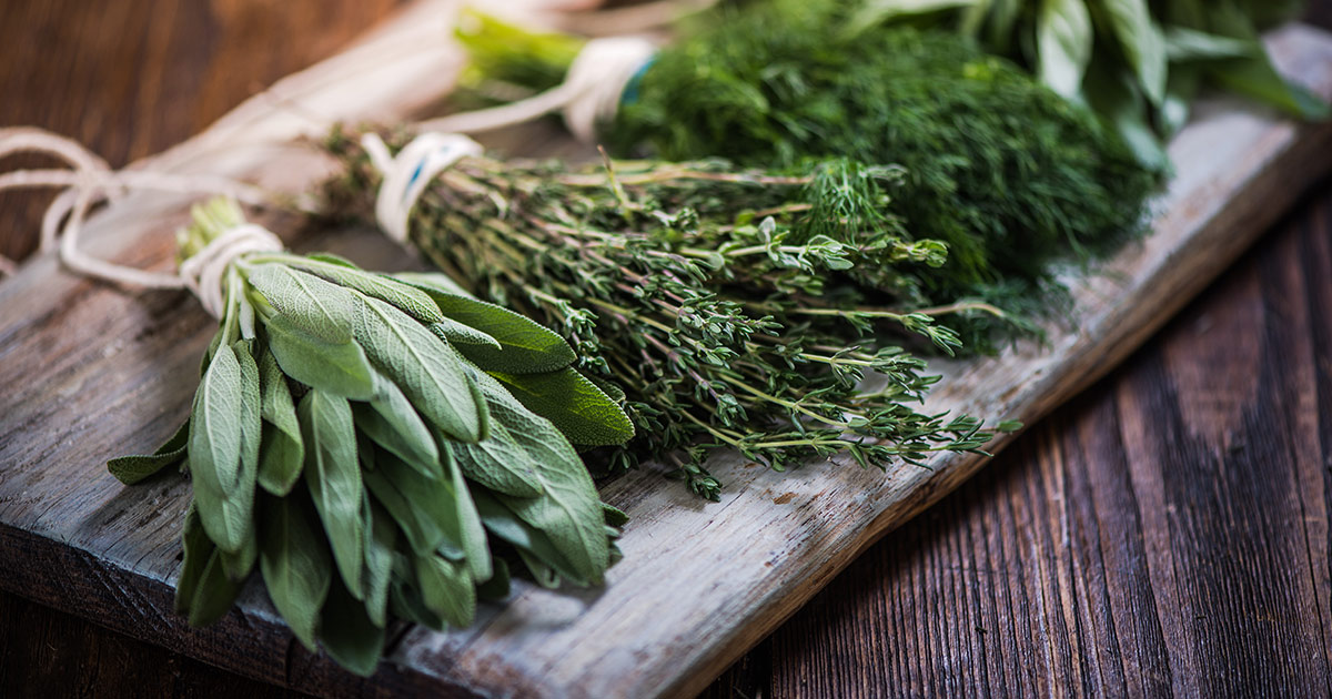 bunches of herbs on wooden surface