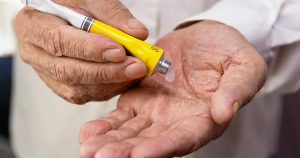 man putting ointment on hands from a tube