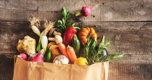 paper bag full of vegetables on wooden surface