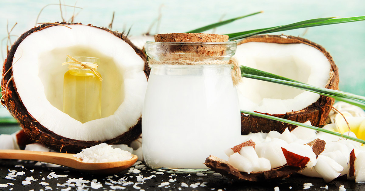 jar of coconut oil beside two coconut halves