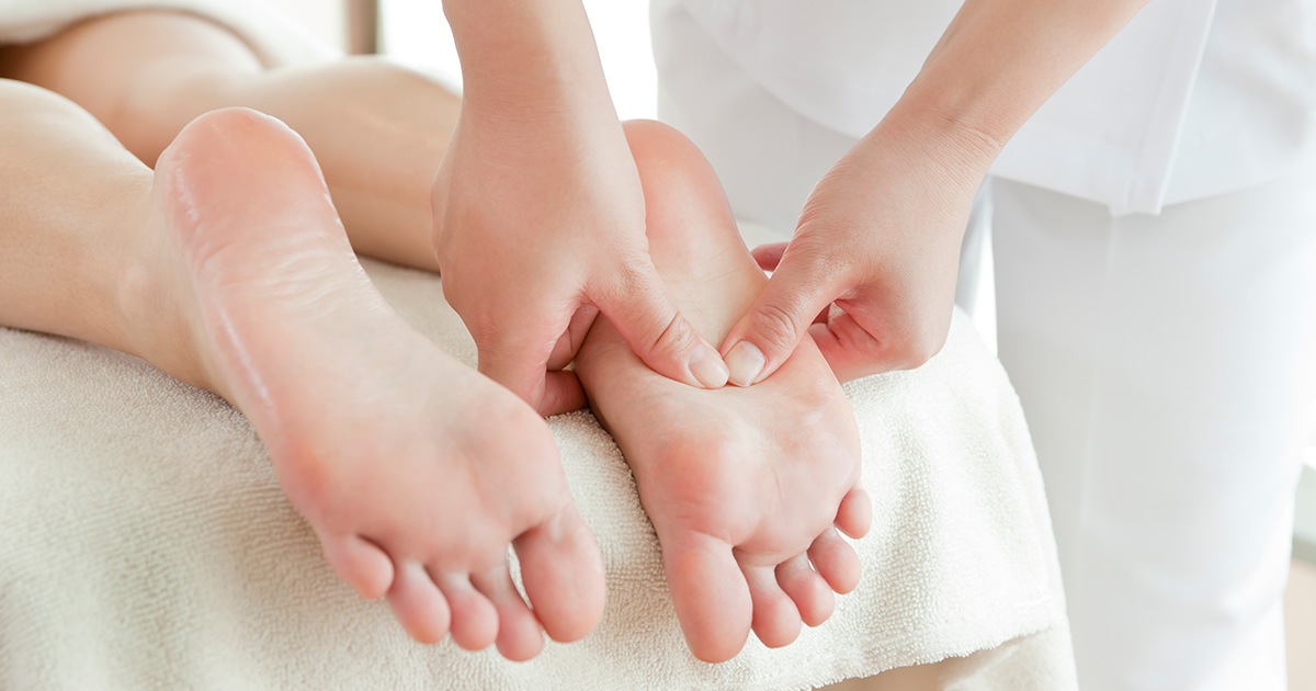 practitioner performing reflexology on a patient