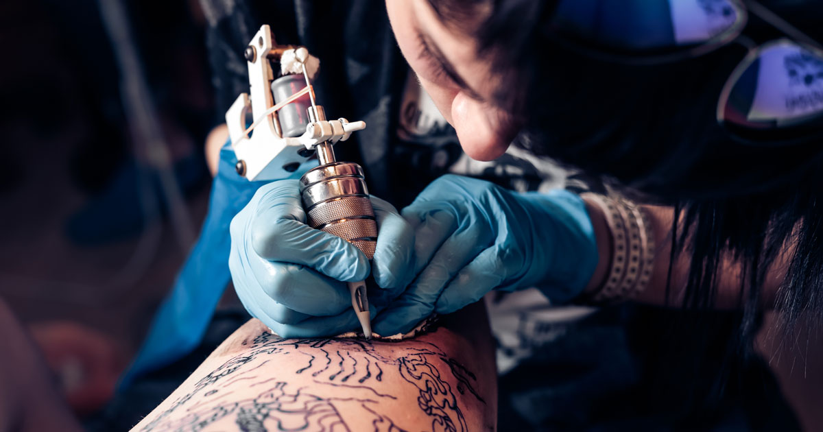 Tattoo artist inking someone's arm