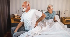 elderly man sitting on edge of bed with hand on lower back