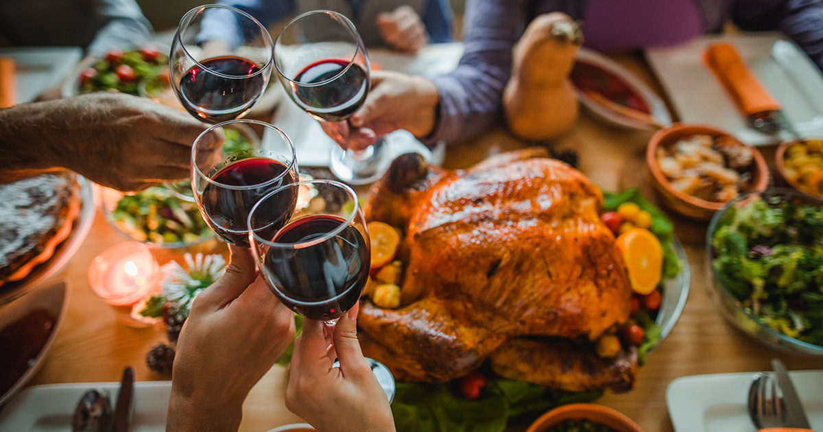 family clinking wine glasses over thanksgiving table