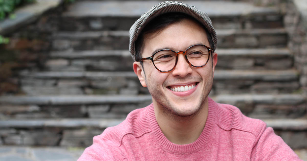 Smiling man wearing eyeglasses and hat