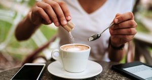 Woman adding white sugar to the coffee