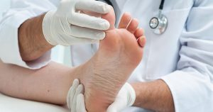 Doctor dermatologist examines the foot