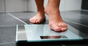 Woman stepping on scale