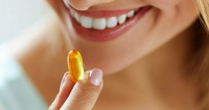 Woman taking gel capsule supplement