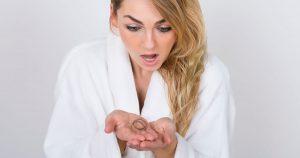 Shocked woman looking at a clump of hair in her hands