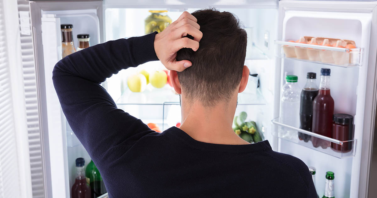 Confused man looking at food in refrigerator