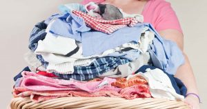 Person holding a laundry basketful of clothes