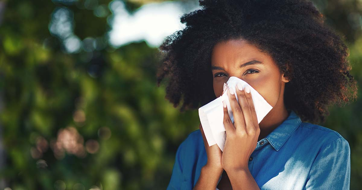 Young woman blowing her nose with a tissue outside