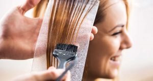 Hairdresser applying hair color to a female client's hair