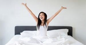 Woman doing morning stretches in bed