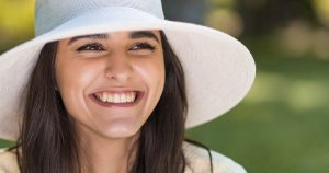 Smiling woman wearing a hat, sitting outside