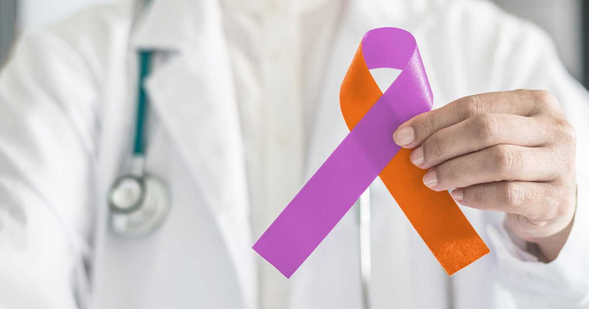 A doctor holding a purple and orange psoriasis awareness ribbon.
